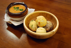 Bread fills a dish sitting next to a bowl of soup.