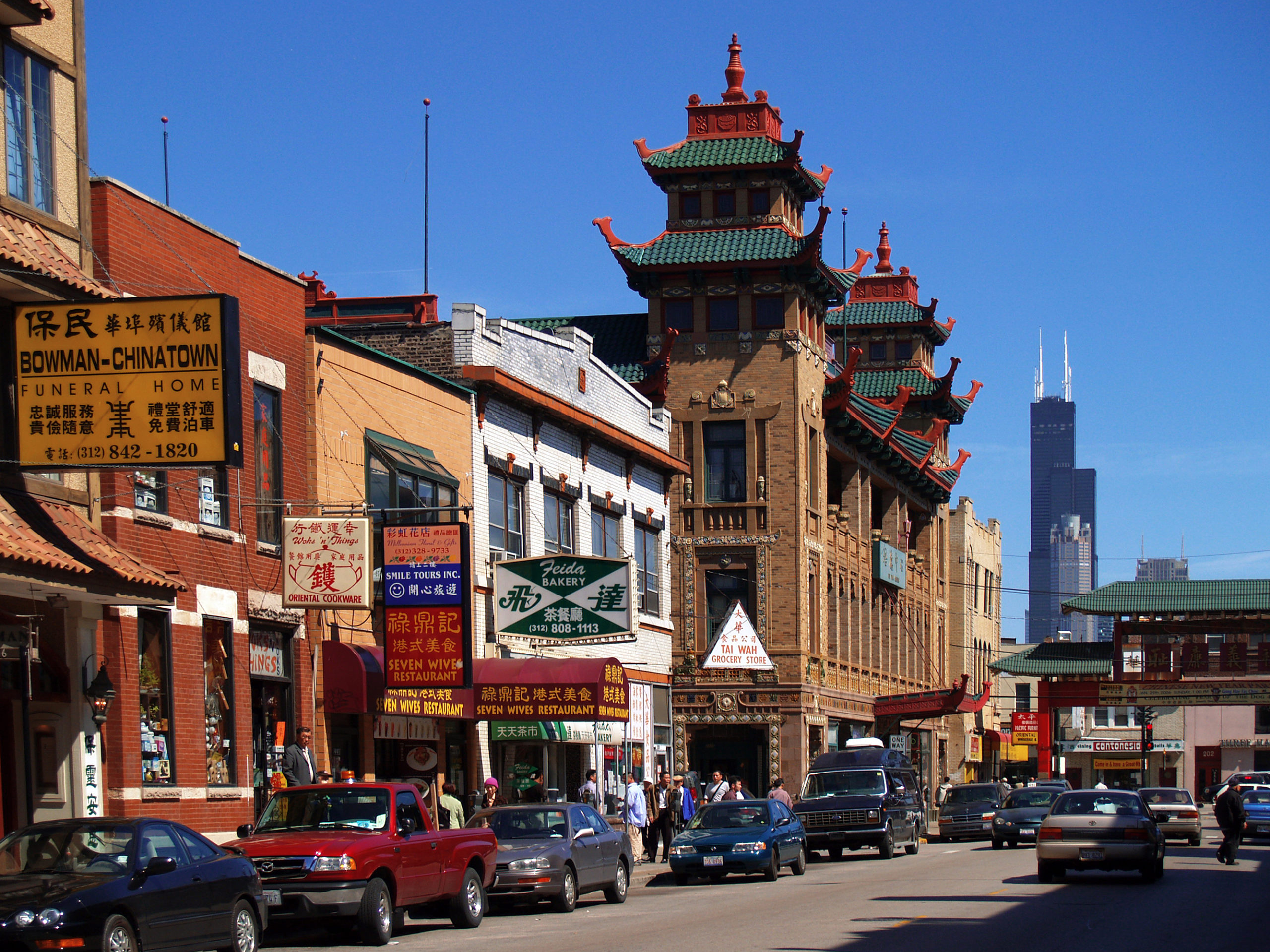 Chicago's Chinatown sits background of the image. A busy street is lined with cars and tall buildings with Chinese architecture sit above them.