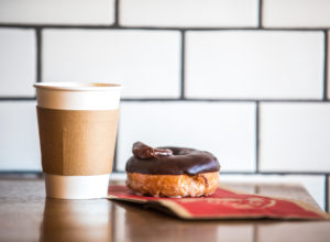 Coffee in a paper cup sits next to a flour donut with chocolate frosting on top.