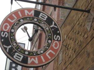 """A donut shaped sign with the copy """"Quimby's"""" wrapped twice around hangs down from a brick buildings"""