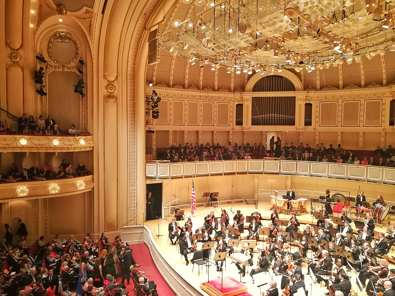The interior of a grand performing arts center is photographed with the Chicago Symphony Orchestra seated on its stage.