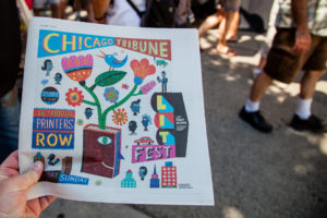 A hand holds a newspaper. Its cover showcases the Printers Row Lit Festival.