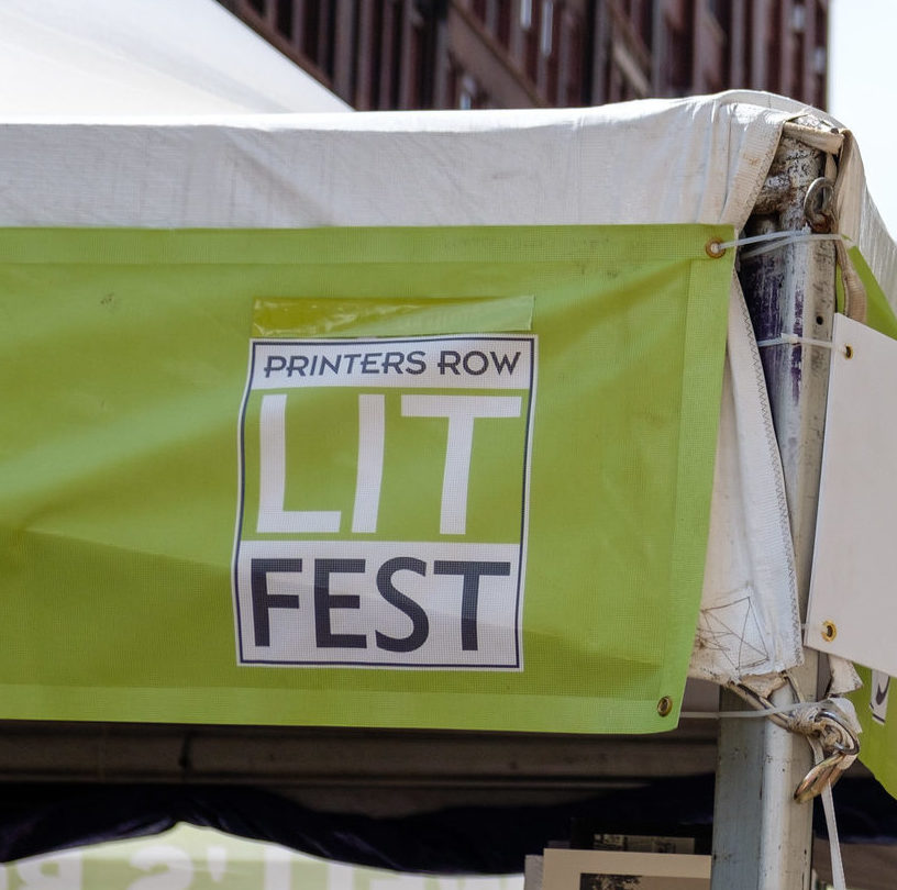 A foreground shot of a promotional sign for the Printers Row Lit Fest is in front of a giant red brick clock tower in the background