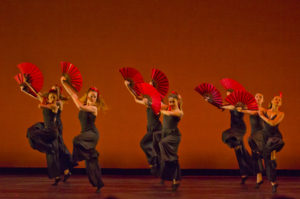 Six ballet dancers dressed in black dressed hold bright red fans in the middle of a dance number.