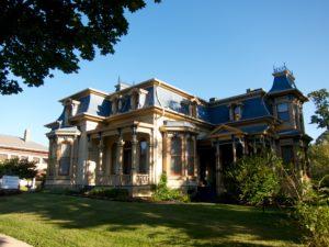 Lush greenery surrounds a lavishly built historic victorian house.